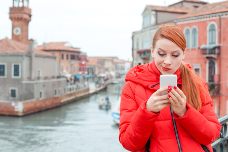 Portrait serious skeptical, worried, displeased young woman reading bad news on smart phone holding using mobile. Irish model in red winter coat, redhead hair standing on Venice urban background