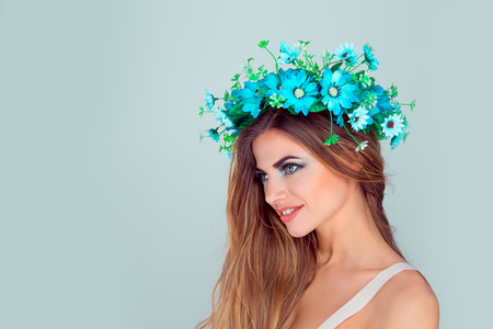 Young beautiful woman, floral crown on head smiling in side profile looking ahead, posing on light green blue studio background with copy space. Multicultural beauty model with headband from flowers.