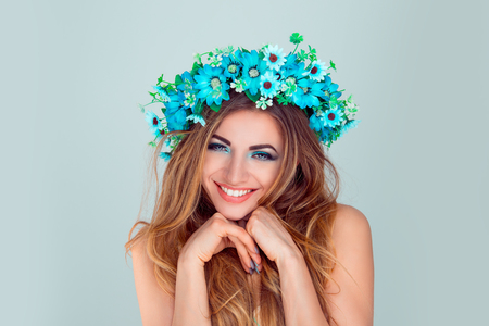 Sexy and playful. Portrait of pretty cheerful stylish cute, charming, nice, woman with headband from flowers, with hand near chin shy, looking at camera with flirting sight isolated on light blue wall Standard-Bild