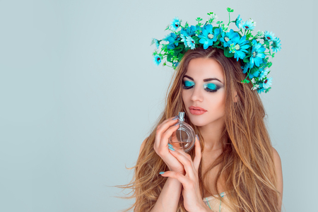 Beautiful young beauty woman with eyes closed, headband of anemone flowers on head with bottle of perfume holding smelling floral sweet aroma of her new perfume concept isolated light blue background