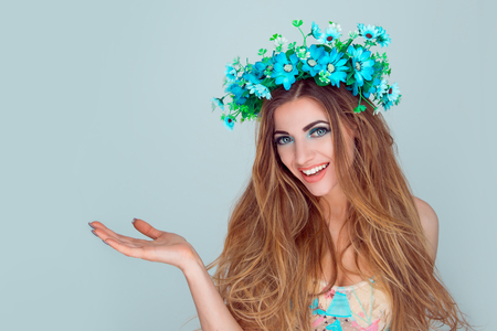 Portrait beautiful young beauty woman wearing floral headband showing empty copy space for your beauty product on open hand palm isolated on light blue background. Anemone wreath of flowers on head.