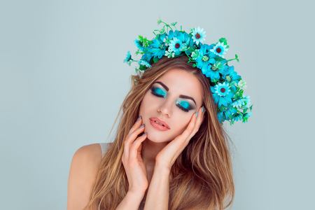 Beautiful young woman smiling model with flowers on head floral headband hairstyle makeup blue green eye-shadow posing with closed eyes isolated on light blue background. Spring hippie bride concept Фото со стока - 119335838