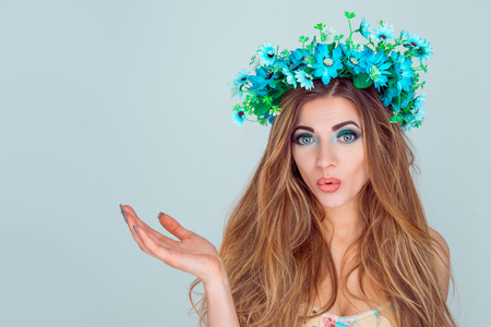 Young surprised woman wearing floral headband pointing with open palm to copy space for your beauty product isolated on light blue background. White cherry blossom wreath of flowers on head girl