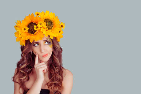 Head shot thoughtful skeptical suspicious young Woman with floral headband looking up to the side. Fashion girl with crown from sunflowers on head doubtful isolated on gray background with copyspace