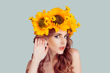 Woman with floral headband hand to ear listening in shock. Closeup portrait of Noisy Caucasian Fashion girl with crown from sunflowers on head hand to ear isolated on gray background with copy space. Stok Fotoğraf
