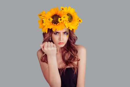 Emotional displeased young Woman with floral headband showing fist in anger isolated over gray background. Fashion girl with crown from sunflowers on head.