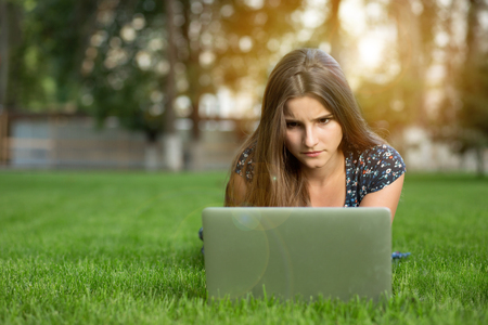Upset female student in front of laptop computer, in college campus, has displeased facial expression, uses free internet outdoors lying down on green lawn headphones on head. Multicultural model.