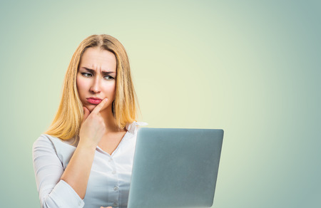 Modern blond thoughtful woman frowning in misunderstanding thinking while using laptop looking at it. Business person in white shirt, long blonde hair isolated on light green yellow studio background.