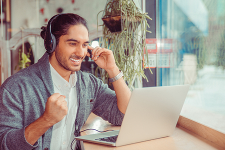 Man smiling having a online conversation looking at laptop screen, cheering, pumping fist gesticulating at home in living room, near window holding headset with hand. Customer service representative.