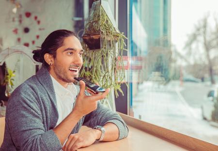 Latijns-Amerikaanse jonge volwassene die spraakherkenning gebruikt op de telefoon. Close-upportret van een knappe man met een formeel wit overhemd en een grijze blouse die bij het raam zit aan een tafel in de woonkamer of de coffeeshop Stockfoto