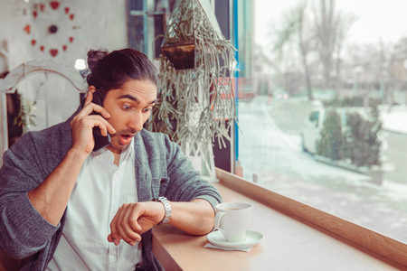 Shocked man checking time, talking on his phone. Closeup portrait of a handsome guy wearing white shirt, gray blouse sitting near window at table in coffee shop. Mixed race, indian turkish model