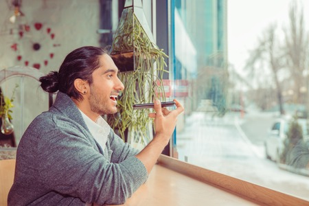 Man use voice recognition with smart phone. Closeup portrait handsome guy wearing formal white shirt, gray blouse sitting near window at a table in living room, coffee shop. Mixed race, indian turkish