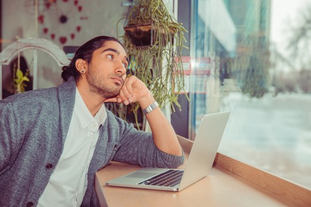Pensive young man in front of the laptop looking up to side thoughtful daydreaming. Closeup portrait of a handsome guy wearing white shirt, gray blouse sitting near window at a table in living room