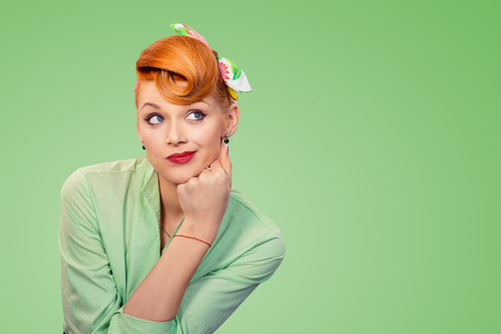 Closeup portrait skeptical confused pin up retro style woman looking suspicious, curiosity on her face mixed with disapproval, isolated on green background. Negative human emotions, facial expressions