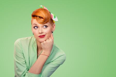 El perno confuso escéptico del retrato del primer encima de la mujer retro del estilo que parece sospechoso, la curiosidad en su cara mezclada con la desaprobación, aislada en fondo verde. Emociones humanas negativas, expresiones faciales.