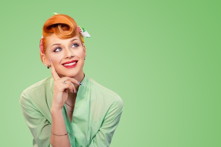 Closeup portrait of charming, smiling joyful, happy, young woman looking upwards daydreaming something nice, thinking isolated on green background. Positive human emotions, facial expressions feelings