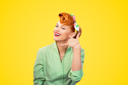 Closeup redhead young woman pretty pinup girl retro vintage 50s style green button shirt winking eye making showing call me sign gesture asking to contact her looking at camera over yellow background