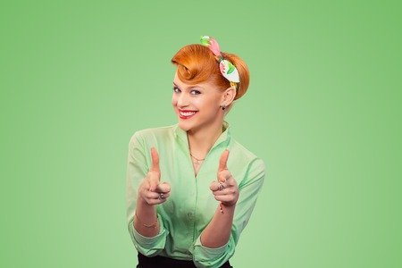 Hey you! Woman red head young woman pretty pinup girl pointing at camera, point index fingers hands like guns gesture isolated on green background. Retro vintage 50s style Emotion face expression.