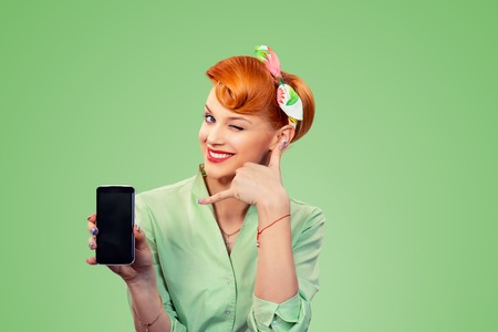 Call me. Closeup redhead young woman cute smiling pinup girl in button shirt holding phone showing call me sign hand gesture looking at camera, retro vintage 50s hairstyle isolated on green background