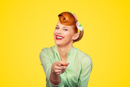 Ritratto di una bella donna pinup stile retrò che punta a te sorridente ridere isolato muro di fondo giallo. Linguaggio del corpo, gesti, psicologia. Concetto di bullismo a qualcuno