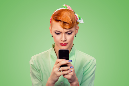 Bad message. Portrait upset unhappy serious woman looking at texting on phone displeased with conversation isolated on green background retro vintage 50's style. Negative emotion face expression