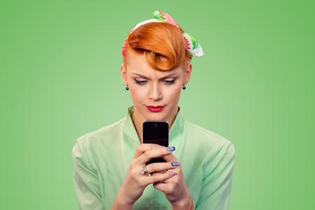 Mal mensaje. Retrato molesto mujer seria infeliz mirando mensajes de texto en el teléfono disgustado con la conversación aislada sobre fondo verde estilo retro de los años 50. Expresión de la cara de emoción negativa