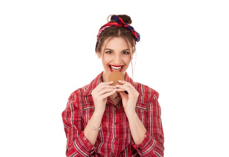Woman eating cookie smiling happy isolated over white background looking at you camera.