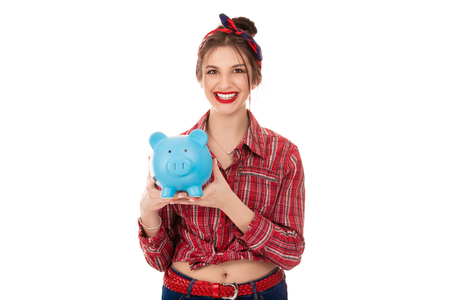 Fröhliche glückliche junge Frau 20er Jahre in Freizeitkleidung mit blauem Sparschwein mit viel Geld isoliert auf weißem Hintergrund