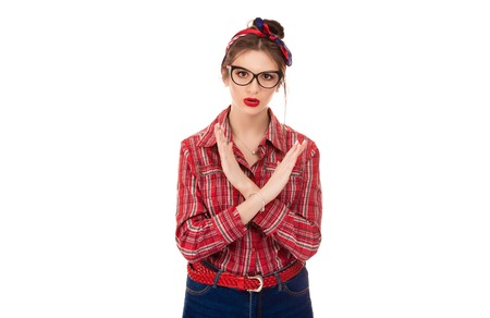 Angry pissed of woman in red checkered shirt and retro bow headband showing stop, no, hands gesture isolated on pure white background Stock Photo