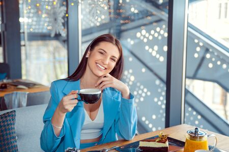 woman sitting at in the living room or a fancy in coffee shop restaurant holding cup of hot beverage tea. Cool young modern female model. Positive face expression emotion