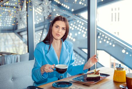 Portrait of a beautiful woman looking frustrated with question in eyes while eating. Hispanic girl wearing formal blue suit sitting at a table in a cafe near the window, metallic staircase background
