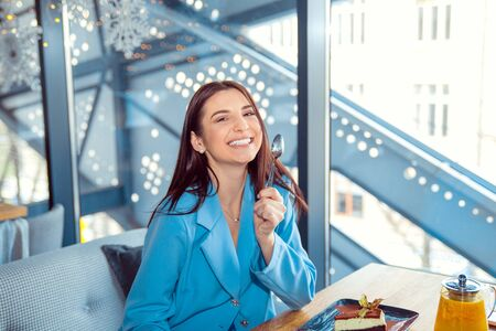 Attractive happy young woman sitting and eating dessert in cafe holding spoon smiling.  Hispanic girl wearing formal blue suit sitting at a table on a coffee shop terrace balcony, staircase background