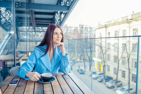 Thoughtful woman at trendy coffee shop juice bar restaurant. Young beautiful model enjoying lunch time cup of coffee tea hot drink thinking. Hispanic girl wearing formal blue suit sitting on a balcony