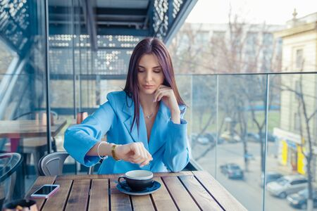 Woman checking time on her wrist watch, waiting for her boy friend being late to rendez-vous. Hispanic girl wearing formal blue suit and white shirt sitting at table on a cafe terrace balcony outside