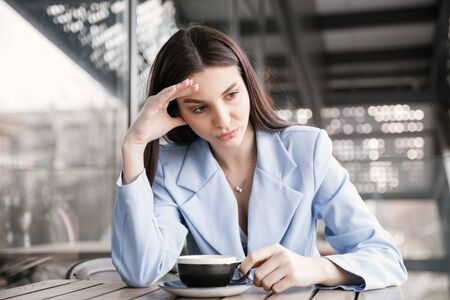 Sad woman in a cafe holding head with hand. Closeup portrait of a beautiful hispanic girl wearing formal blue suit sitting at a table on a cafe terrace balcony outside staircase background