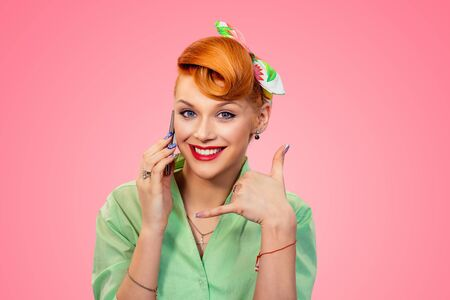 Call me. Closeup red head young woman pretty smiling pinup girl in green button shirt talking by phone showing call me sign hands gesture looking at you camera, retro vintage 50s hairstyle over pink Banco de Imagens