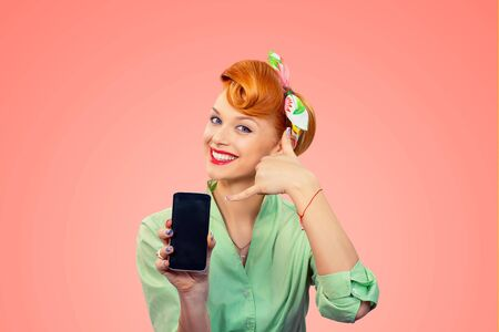 Call me. Closeup redhead young woman pretty smiling pinup girl green button shirt showing phone screen giving call me sign hands gesture looking at you camera, retro vintage 50s hairstyle on pink