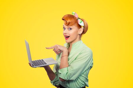 Girl showing laptop. Closeup redhead beautiful young woman pretty excited, amazed smiling pinup girl green button shirt pointing finger to pc looking at camera, retro vintage 50's hairstyle on yellow Фото со стока