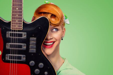 Woman pinup girl with electric acoustic rock guitar smiling happy isolated on green background. Retro vintage hairstyle.