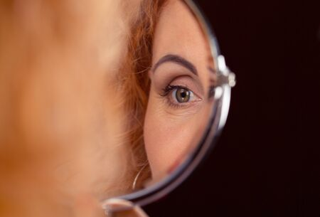 Female, woman's eye reflected in a round small mirror. Vision and ophthalmology concept Banco de Imagens - 130262907