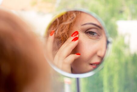 Reflection in the mirror. A woman looks in the mirror noticing the first wrinkles, signs of aging. Anti-aging treatment concept Banco de Imagens