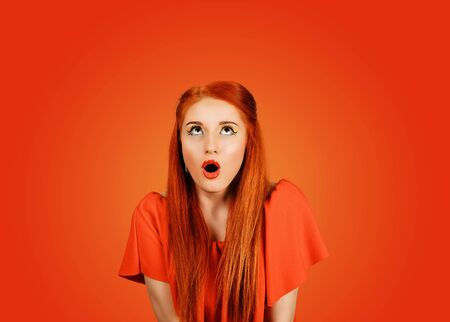 Portrait of young woman with shocked facial expression looking up to the copyspace isolated on red background Banco de Imagens
