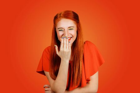 Happy woman laughs and covers her mouth with hand isolated on red background Banco de Imagens - 130262923