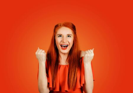 Happy successful student, euphoric woman winning, fist pumped, celebrating success isolated on Red background