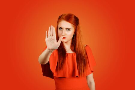 Pretty teen girl, young woman making a gesture stop with her hand isolated on a red background 写真素材