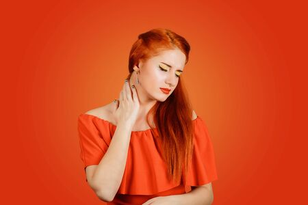 Closeup of a girl having neck pain massaging it to relieve the ache isolated on a red background. Sick young woman having a sore throat