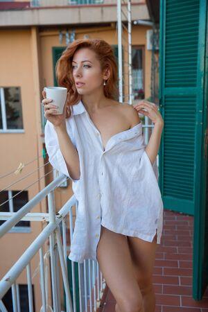 Mooie roodharige vrouw met lang krullend gemberhaar in wit overhemd die 's ochtends koffie drinkt op een Italiaans balkon. Verticale afbeelding, portret in natuurlijke kleuren. Stockfoto
