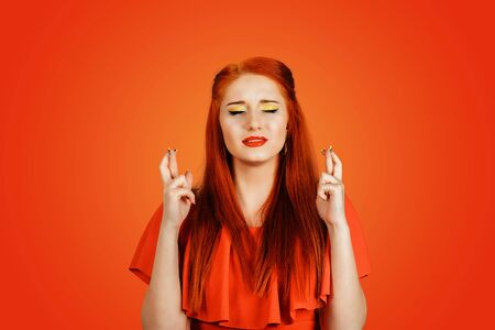 Redhead woman holds her fingers for luck. Closeup portrait of beautiful dreamy girl wearing red dress crossing fingers with closed eyes wanted to make her wishes come true Isolated on red background Banco de Imagens