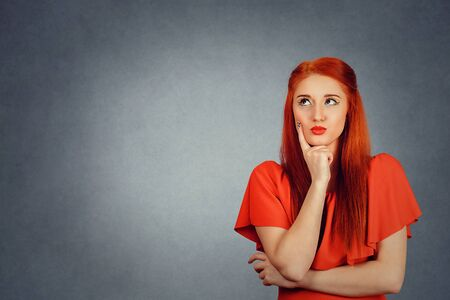 Thoughtful Gorgeous young redhead woman wearing red dress and yellow makeup thinking, looks up to right side, hand on cheek isolated on gray background