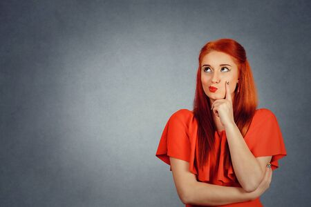 young redhead woman wearing red dress and yellow makeup saw something interesting on the right side up confused skeptical woman girl female thinking  isolated on gray wall background copy space Banco de Imagens
